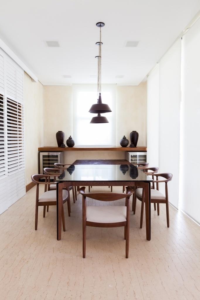 A sala de jantar é um ambiente de permanência, para refeições, mas também serve de passagem entre cozinha (esq.) e varanda (dir.). A mesa estruturada em aço revestido por madeira e com tampo em mármore é assinada por Jader Almeida e foi combinada às cadeiras de madeira Aristeu Pires (Dpot). A iluminação é feita com pendentes (La Lampe) com focos reguláveis. O projeto de decoração da casa de campo em Itu (SP) é do escritório Dípticos