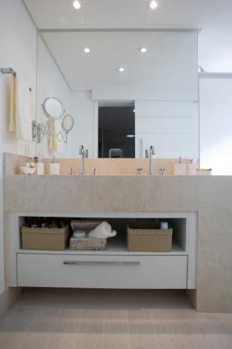 O escritório Arquitetura 8 ampliou a área de 3,3 m² do antigo banheiro da suíte máster ao reduzir um dos quartos. O ambiente, após a reforma, passou a contar com área de 5,5 m². A distribuição dos espaços e a porta de correr (refletida no espelho) contribuíram para a sensação de amplitude
