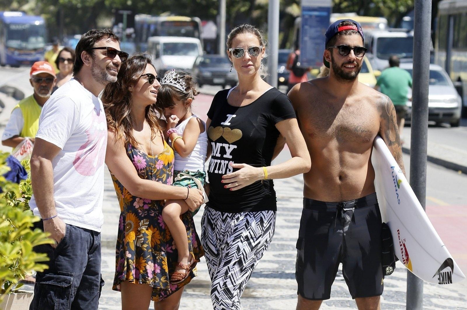 24.mar.2015- Grávida de gêmeos, Luana Piovani vai à praia do Leblon com Pedro Scooby e encontra Marcelo Faria com a esposa Camila Lucciola e a filha