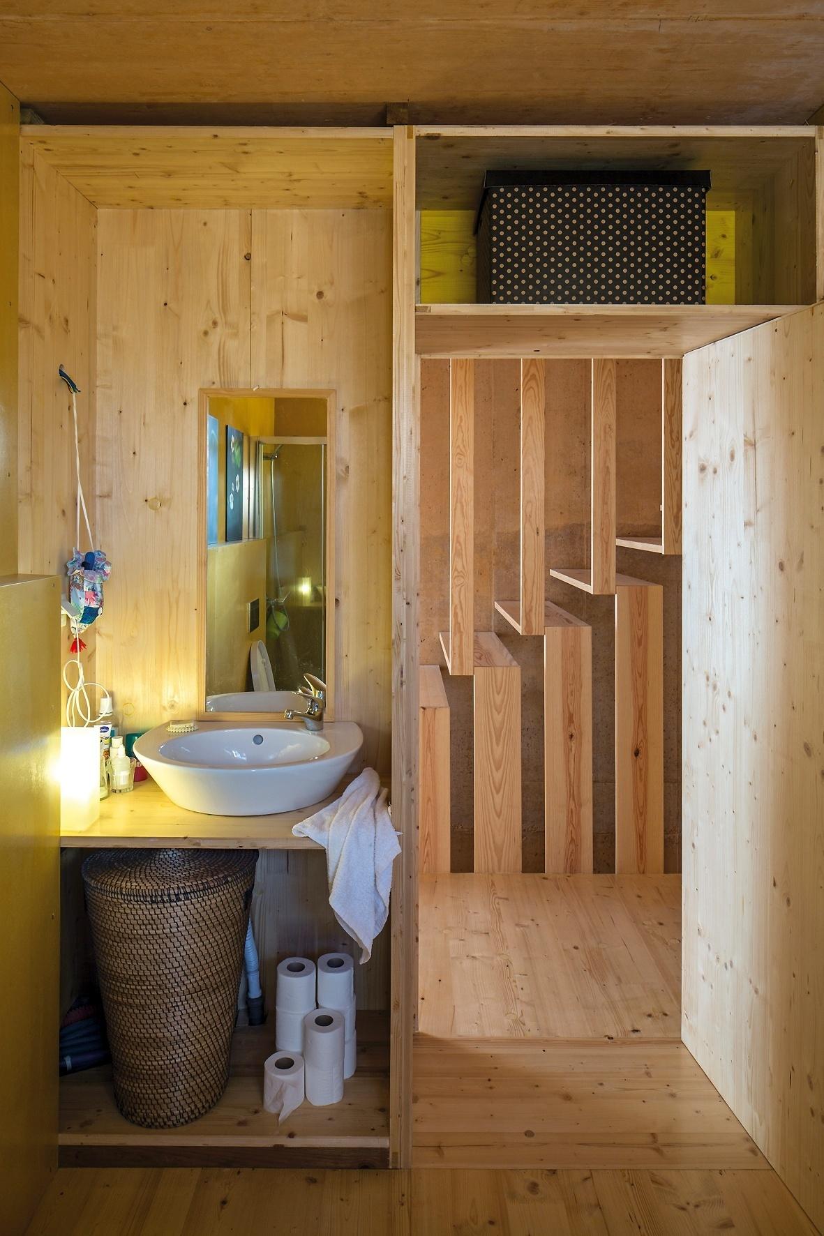 A madeira reutilizada da concretagem da fachada reveste, não só os eixos de circulação entre os três pavimentos da Casa do Zé, mas também as áreas
