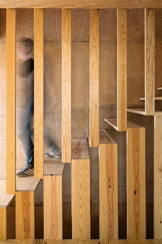 Nas escadas, tábuas horizontais formam os degraus e estão chumbadas por um de seus lados à parede de concreto, sendo, no outro extremo, sustentadas pelo sistema estrutural de lâminas verticais. A disposição que intercala vazios dá leveza e estabilidade ao eixo de circulação entre os pavimentos da Casa do Zé, em Portugal. O plano vertical, ainda, filtra a luz de um jeito especial e funciona como guarda-corpo. A residência tem projeto do escritório Paratelier