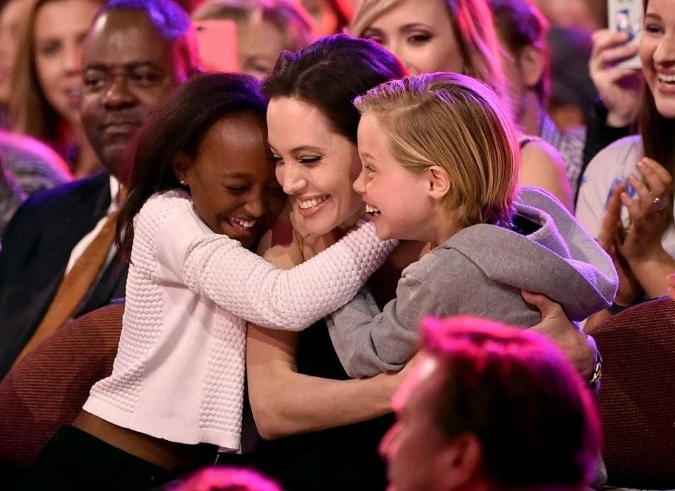 """28.mar.2015 - Angelina Jolie é abraçada pelas filhas Zahara (à esq.) e Shiloh, ao vencer a categoria vilão favorito, por """"Malévola"""", no Nickelodeon Kids' Choice, em Los Angeles. Essa é a primeira aparição pública da atriz após anunciar sua cirurgia de retirada de ovários, para prevenção de câncer"""