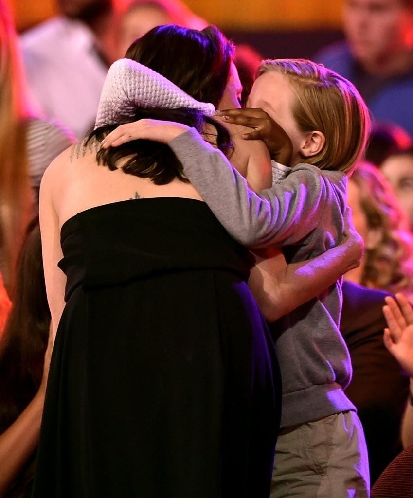 28.mar.2015 - Jolie levanta para receber o prêmio de vilão favorito no Nickelodeon Kids' Choice, em Los Angeles, enquanto é abraçada pelas filhas
