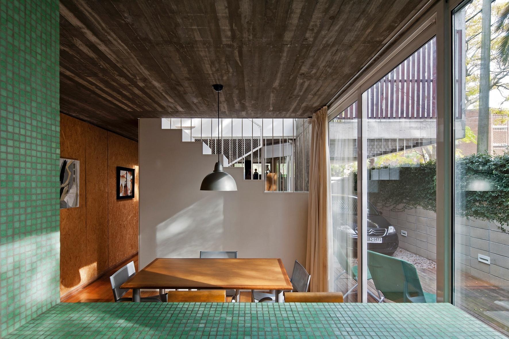 A cozinha americana se comunica com o jantar (ao fundo) por uma bancada alta, revestida por pastilhas verdes, e o jantar está integrado ao deck externo, por portas de correr (à dir.) que criam continuidade para o ambiente social. Nas paredes, o revestimento em OSB 'quebra' a frieza da laje de concreto exposta. A Casa Buceo tem projeto dos arquitetos Marcelo e Martín Gualano e fica em Montevidéu, Uruguai
