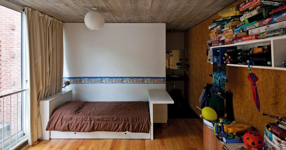 No quarto da criança, madeira no piso, OSB nas paredes um fundo branco que separa dormitório do banheiro, onde a pia  está levemente deslocada para fora (à dir.). A janela do piso ao teto (à esq.) pediu proteção por guarda-corpo na Casa Buceo, com  projeto dos arquitetos Marcelo e Martín Gualano, em Montevidéu, Uruguai