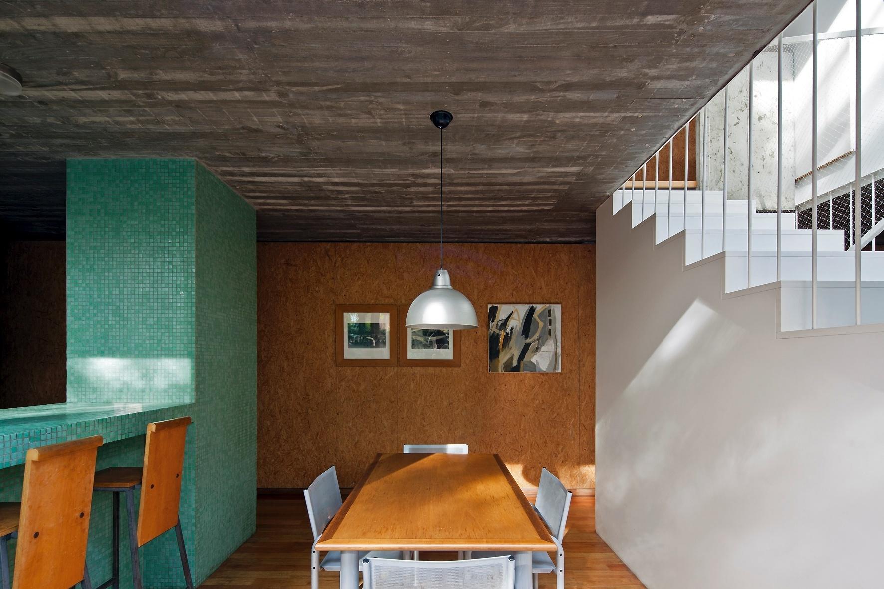 A sala de jantar, entre a cozinha e as escadas, dissolve seus limites através das portas de correr que a ligam ao jardim e pelo eixo vertical para o pavimento superior (à dir.). A Casa Buceo tem projeto dos arquitetos Marcelo e Martín Gualano e fica em Montevidéu, Uruguai