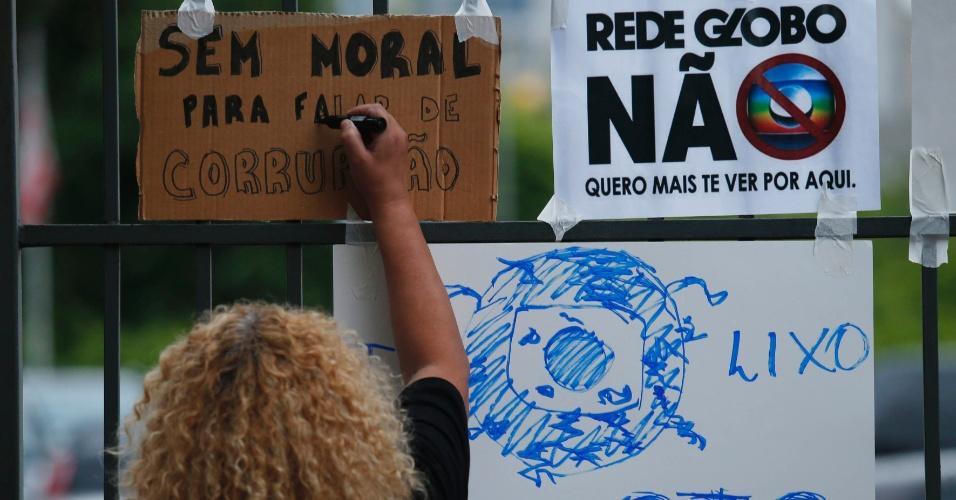 1.mar.2015 - Manifestantes colam cartazes na sede da Rede Globo em São Paulo. Protestos contra a emissora aconteceram em várias capitais, como São Paulo, Rio e Brasília