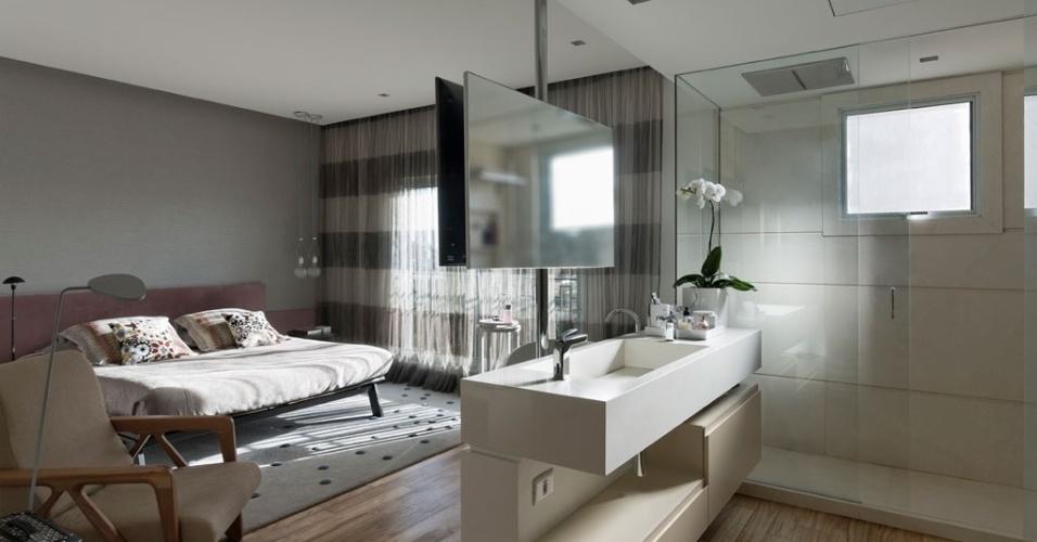 """[FINALISTA] Prêmio Casa Claudia Design de Interiores 2015 - categoria """"Apartamentos"""": Sandra Picciotto. Na suíte, um tubo suspende o espelho do banheiro e a TV do dormitório e torna-se o delimitador desses ambientes amplamente integrados, inclusive, pela contunidade do piso"""