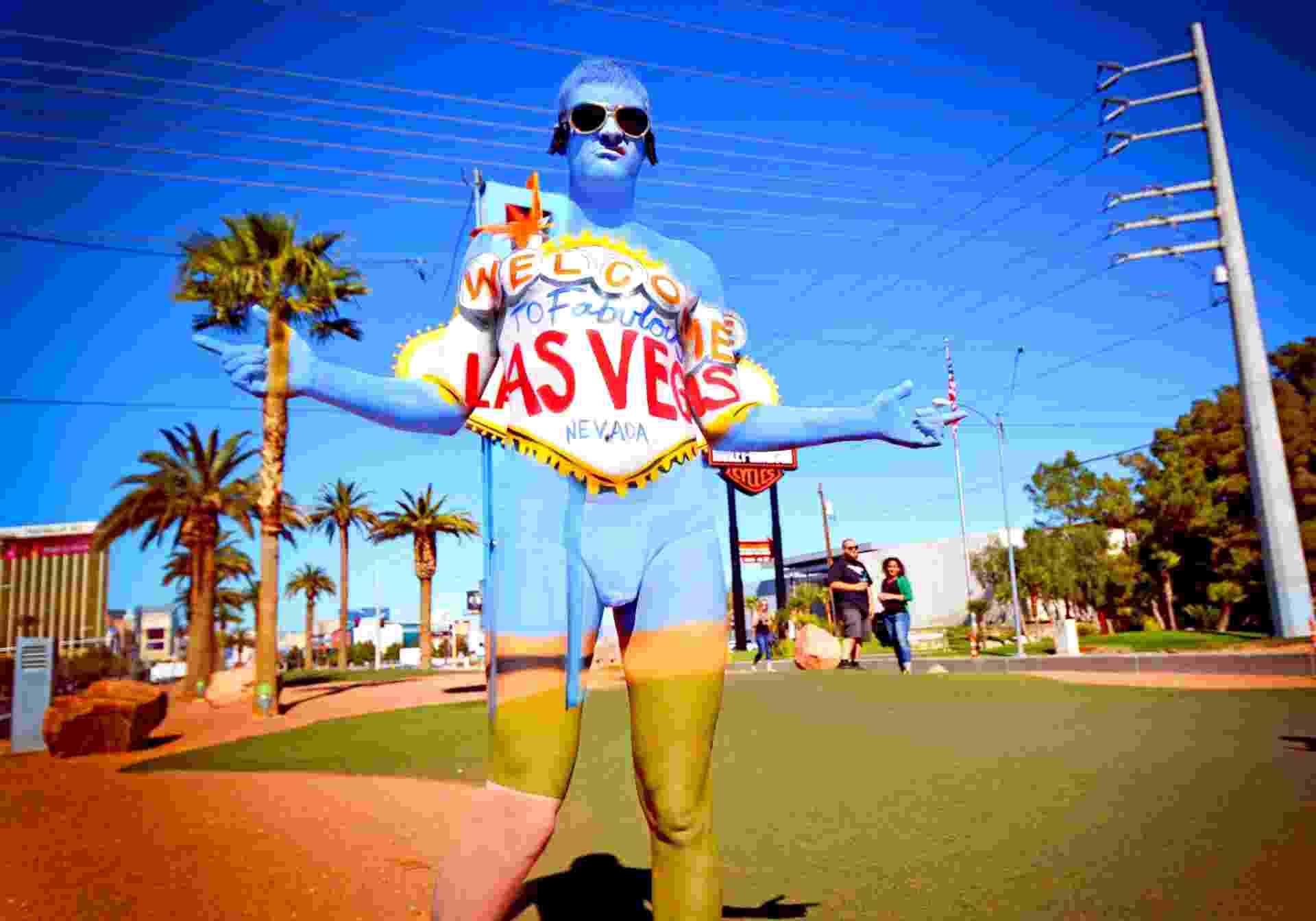 """A artista Natalie Fletchers, especializada em pintura corporal, está viajando pelos Estados Unidos e transformando pessoas em paisagens. Aqui, ela """"insere"""" a pessoa na famosa placa de boas-vindas da cidade de Las Vegas - Caters News/The Grosby Group"""