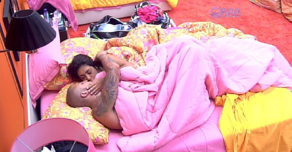 """4.abr.2015 - Amanda, Fernando e Cézar dormem no quarto laranja, na manhã deste sábado, quando são despertados pelos robôs do programa. Desta vez, o vídeo mostra os RoBBBs desafinando durante uma animada """"participação"""" no """"The Voice Brasil"""". Amanda e Fernando continuam deitados na cama com os olhos fechados. Pouco depois, ambos se beijam"""