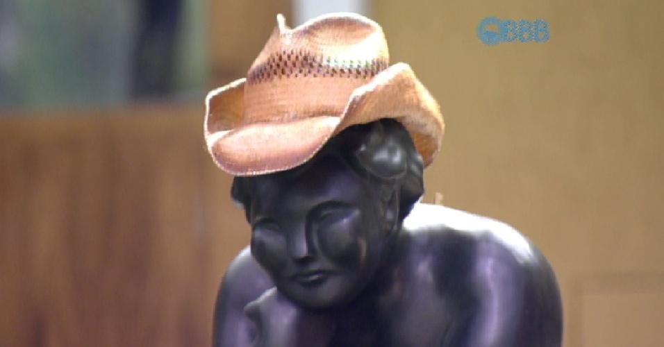 """5.abr.2015 - Cézar chega à área externa da casa e cumprimenta a estátua: """"Bom dia, Fidêncio, meu amiguinho. Você está bem?"""" O brother, então, coloca seu chapéu sobre a cabeça da escultura"""