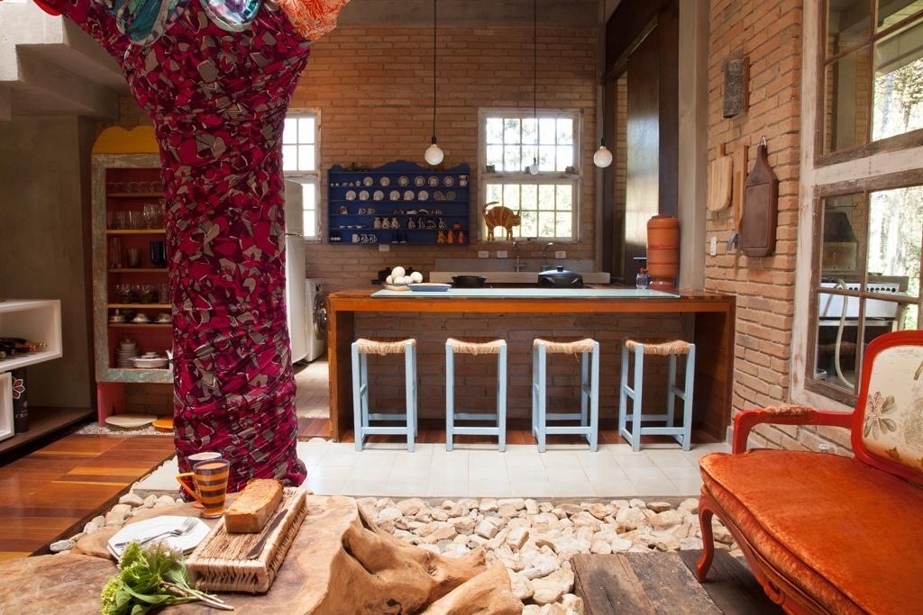 Integrada à área social, construída em torno de um pátio interno elaborado para que a pereira (à esq.) fosse mantida, a cozinha com 10 m² foi delimitada pelo balcão de alvenaria, mesa com tampo de taco e banquetas caipiras. O projeto é de Evelin Sayar