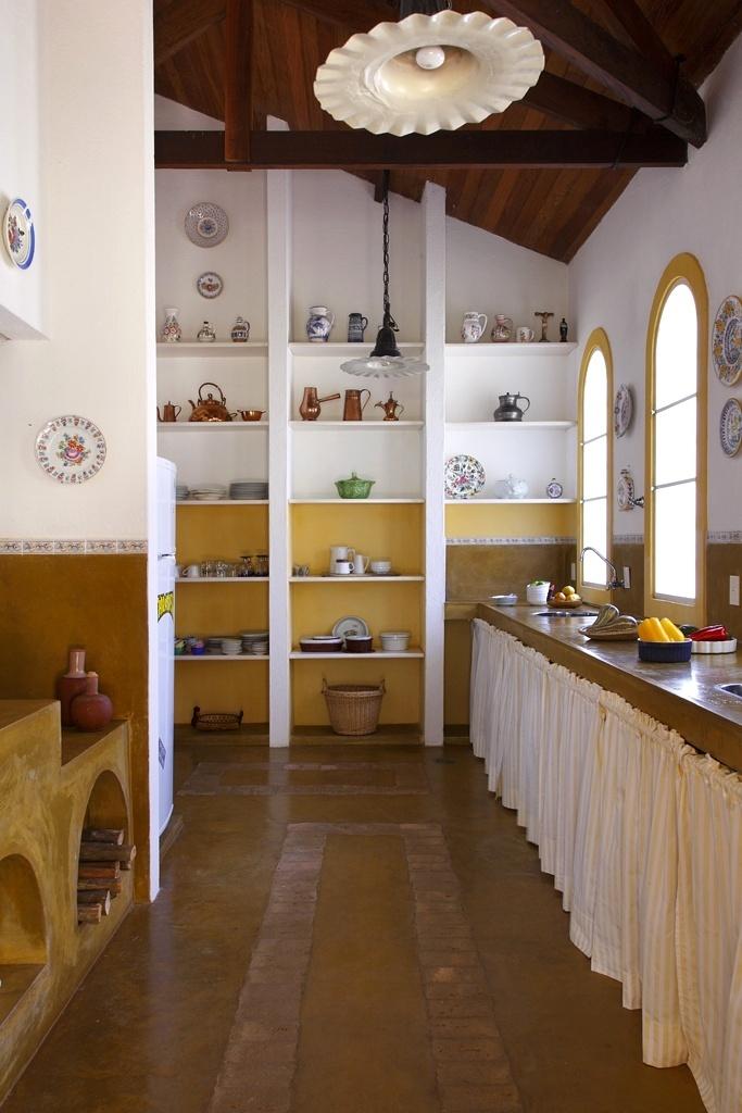 A cozinha com 32 m² segue as mesmas linhas da versão rústica e externa (fotos 13 a 15) idealizada pela designer Vilma Meirelles. As paredes foram pintadas de ocre e branco, têm barrado composto por tozetos, sustentam uma coleção de pratos decoraticos e prateleiras simples, encaixadas em pilares