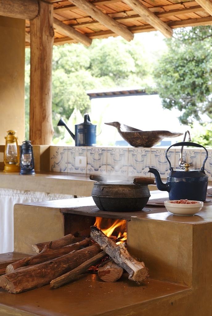 No projeto da designer Vilma Meirelles, o fogão a lenha está posicionado junto à pia, que também leva acabamento de cimento queimado e frontão azulejado