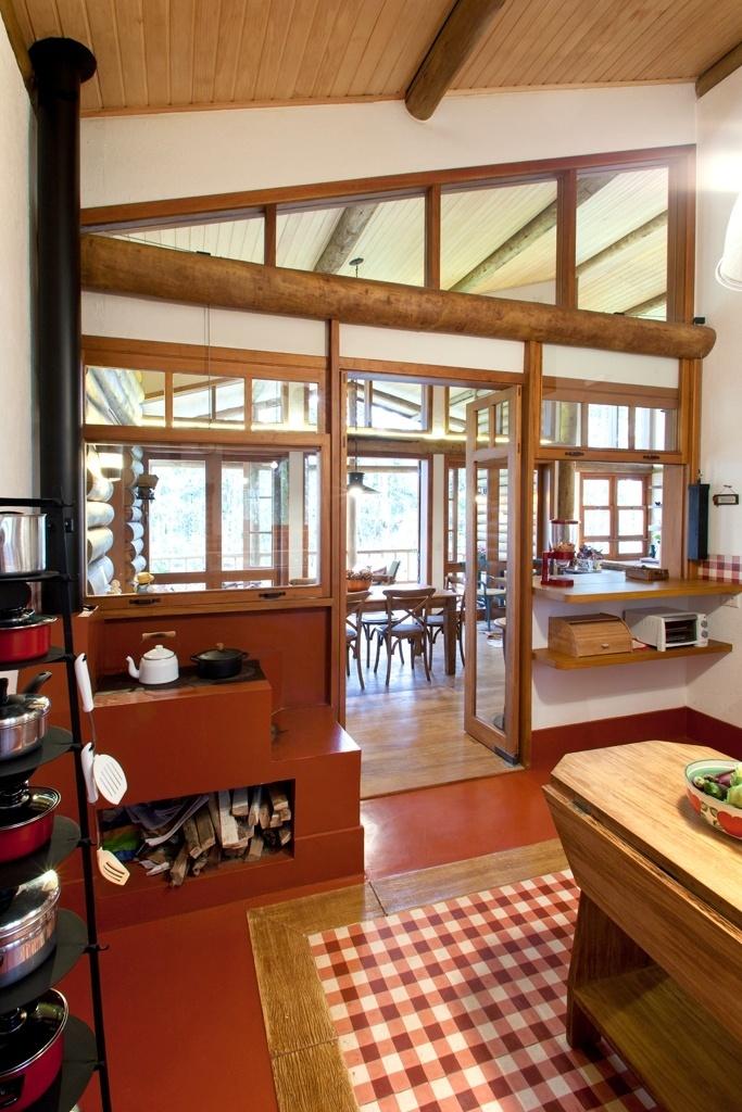 A cozinha planejada pela arquiteta Suzy Melo para esta casa de campo está integrada à área de jantar por janelas guilhotina e pela porta de vidro. Deste ângulo é possível observar a estrutura aparente de madeira, o pé-direito e o forro de madeira que reforçam o estilo rústico do projeto. Note, ainda, que embaixo de uma das esquadrias, o vão foi aproveitado para a instalação de uma pequena prateleira