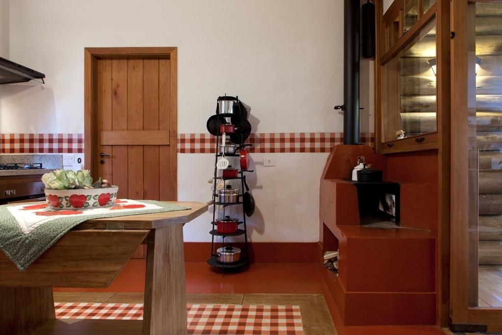 Idealizada pela arquiteta Suzy Melo, esta cozinha com 16,5 m² fica em uma casa de campo. Nela, o cimento queimado vermelho recobre o piso e o fogão a lenha e é combinado ao ladrilho hidráulico em padrão vichy (Dalle Piagge), inspirado na cortina do antigo sítio da família, que - aliás - foi o ponto de partida do projeto. O revestimento faz ainda um barrado na parede e, no chão, é contornado pela borda cimentícia que reproduz o aspecto da madeira