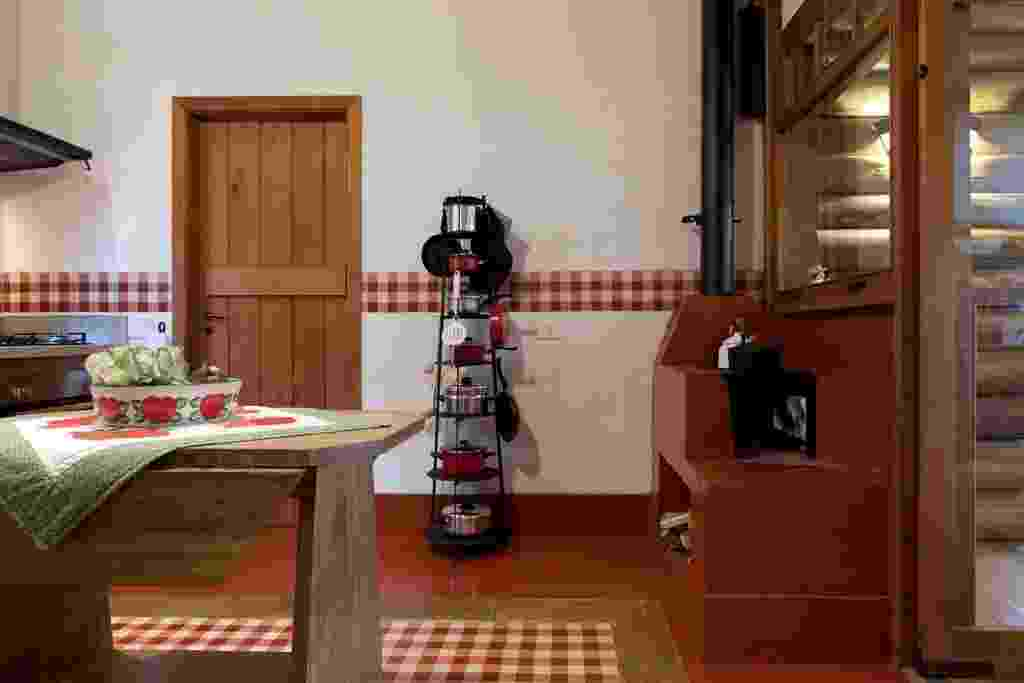 Idealizada pela arquiteta Suzy Melo, esta cozinha com 16,5 m² fica em uma casa de campo. Nela, o cimento queimado vermelho recobre o piso e o fogão a lenha e é combinado ao ladrilho hidráulico em padrão vichy (Dalle Piagge), inspirado na cortina do antigo sítio da família, que - aliás - foi o ponto de partida do projeto. O revestimento faz ainda um barrado na parede e, no chão, é contornado pela borda cimentícia que reproduz o aspecto da madeira - J. Vilhora/ Divulgação