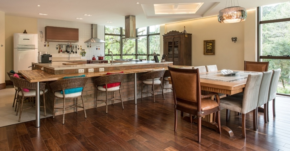 Com 25 m², esta cozinha assinada pela arquiteta Rosa Dalledone faz parte de uma casa de fazenda com proposta rústico-contemporânea. O ambiente está integrado à sala de jantar, diferenciando-se por meio do piso e da bancada que divide os dois ambientes. Revestida de litocerâmica e com tampos superior de Corian e, de refeições, em madeira teca, a estrutura é complementada por cadeiras de fibra. À direita, o fogão a lenha, instalado ao lado do convencional, se beneficia da luz que vem da janela