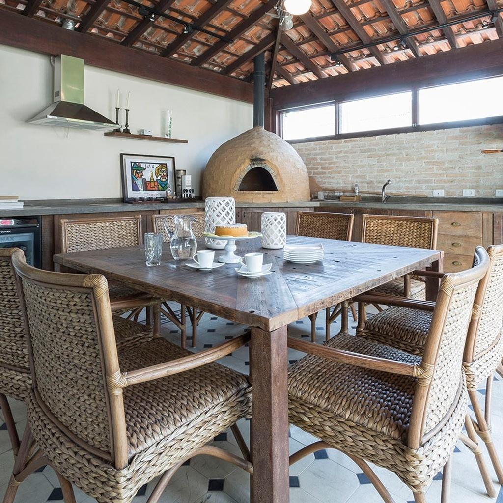 Deste ângulo da cozinha, idealizada por Mariana Noronha e Samra Akad, se pode ver a parede de tijolos e os armários em madeira rústica. O piso foi forrado com cerâmica da Euroville e tosetos mais escuros