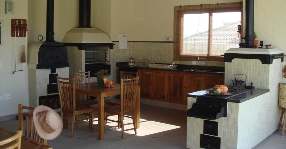 Integrada à varanda e ao interior da morada, esta cozinha com 21 m² foi projetada pela arquiteta Maria Gloria Batista em estilo rústico. Para dar praticidade ao espaço, uma parte da parede, o fogão, o forninho e a churrasqueira foram revestidos com pastilhas cerâmicas, que criam um fundo para o tampo de granito. A base clara e o piso neutro de porcelanato destacam, ainda, a madeira empregada nos móveis e forro