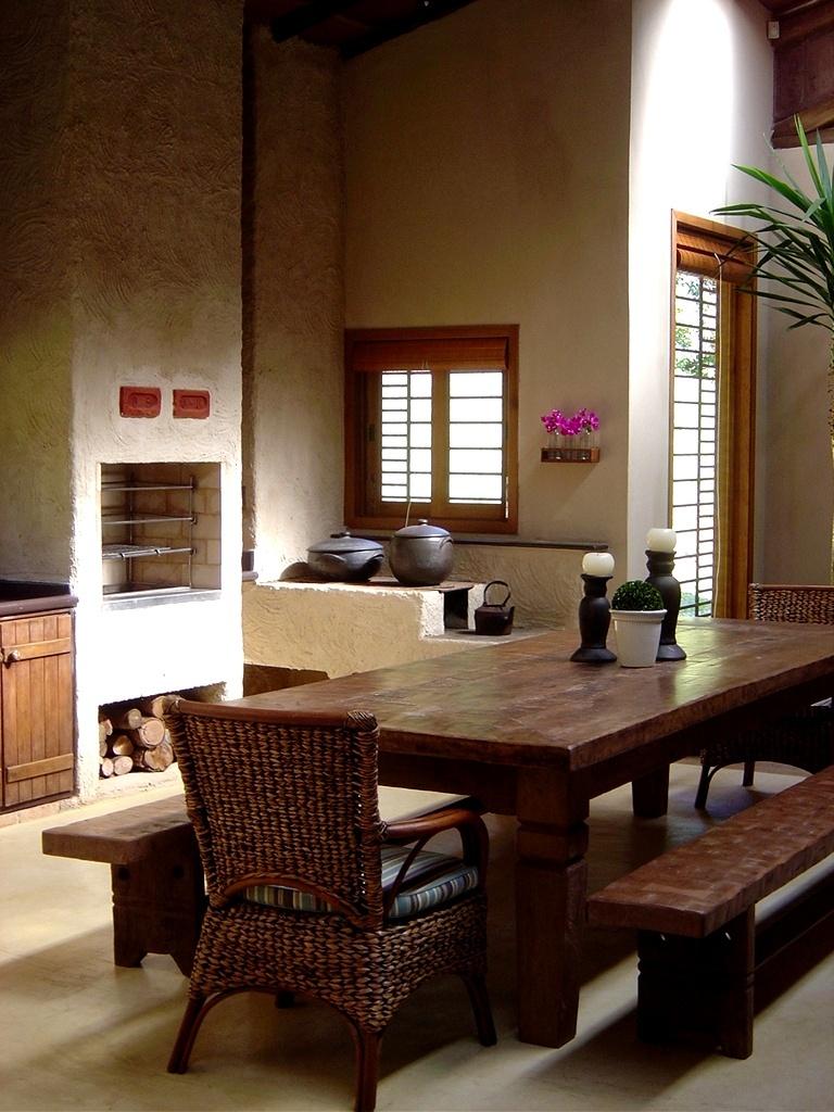A cozinha rústica projetada pela arquiteta Paula Gambier tem mesa complementada por dois bancos e duas poltronas de fibra natural, que enfatizam a simplicidade da proposta. Ao fundo, a churrasqueira e o fogão a lenha compõem uma central de cocção. Esquadrias de madeira destacam-se sob o amplo pé-direito com superfície lisa que contrasta com as paredes rugosas