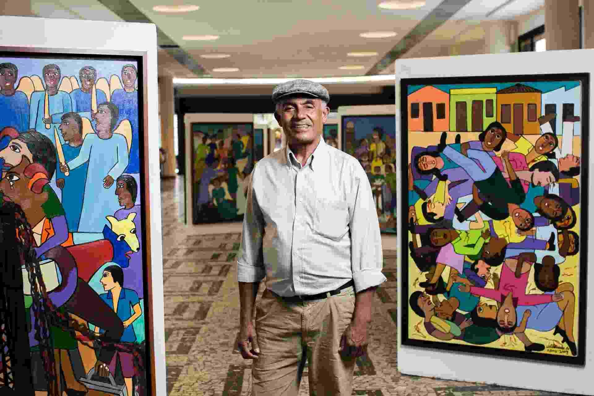 O pintor primitivista Waldomiro de Deus posa entre suas obras, em exposição no Conjunto Nacional - Leonardo Soares/UOL