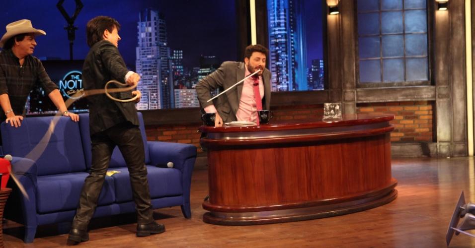 """9.abr.2015 - Xororó brinca com Danilo Gentili no """"The Noite"""" e tenta acertar cigarro na boca do apresentador usando um chicote"""