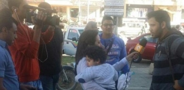 Lamia Hamdin foi fotografada enquanto gravava entrevistas com o filho pequeno no colo - Al-Watan