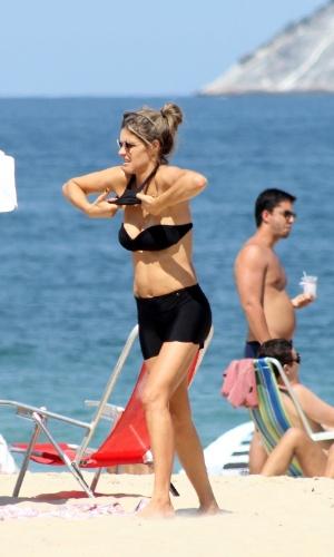 12.abr.2014 - Fernanda Lima tira blusa para aproveitar dia na praia do Leblon, no Rio de Janeiro
