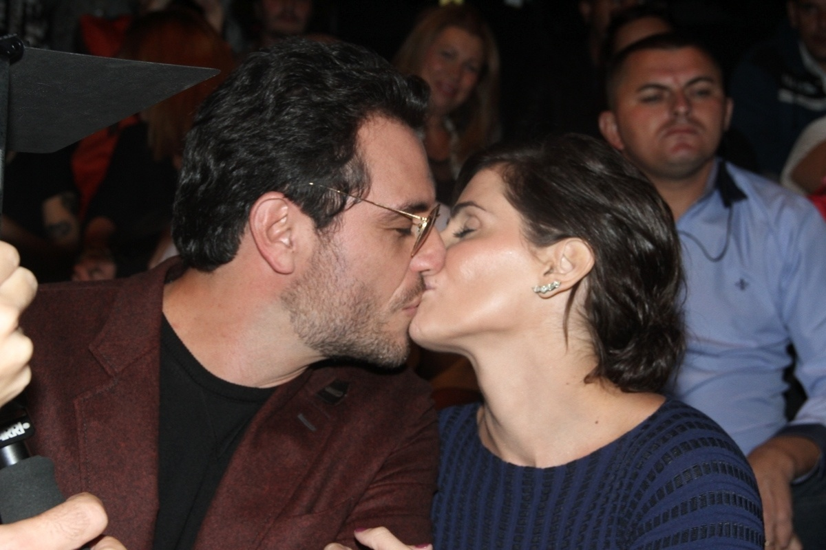 14.abr.2015 - Na plateia do segundo dia de fesfiles da São Paulo Fashion Week, Rodrigo Lombardi troca beijos com Deborah Secco durante as gravações da novela