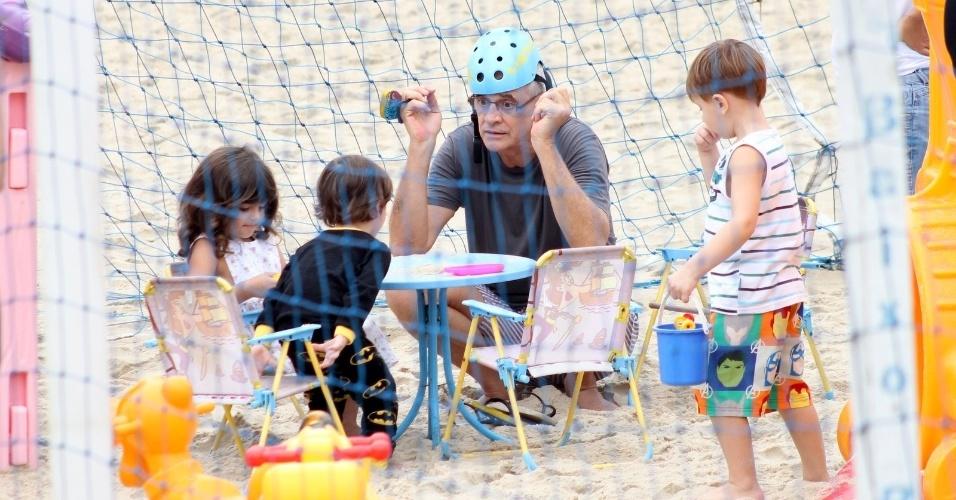 19.abr.2015 - Quem topa colocar o capacete e brincar agachado na areia é sempre o vovô, não é mesmo? Na família de Marcos Caruso não é diferente. Neste domingo, o ator, diretor e escritor foi fotografado no Baixo Bebê -- no Leblon, no Rio de Janeiro, com os netos