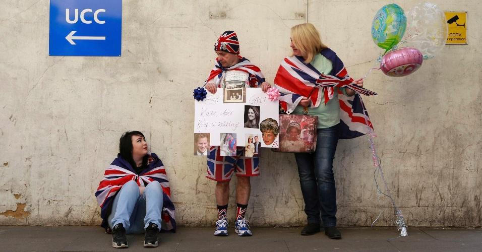 """21.abr.2015 - Enrolados na bandeira do Reino Unido, fãs da realeza aguardam o nascimento do segundo filho de Kate Middleton e do Príncipe William em frente à ala Lindo do hospital St. Mary, em Londres. Os três levaram um cartaz que dizia """"Kate, não nos deixe esperando"""""""