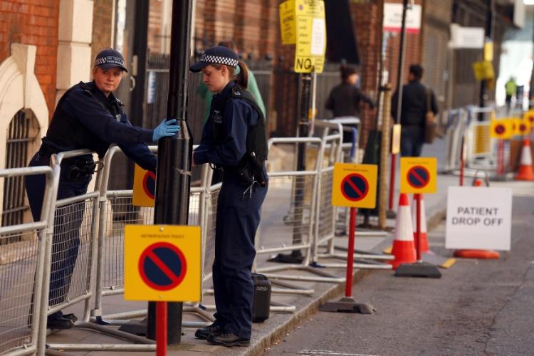 21.abr.2015 - Policiais checam grades de segurança colocadas em frente à ala Lindo do hospital St. Mary, em Londres, onde deve nascer o segundo filho de Kate Middleton e do Príncipe William