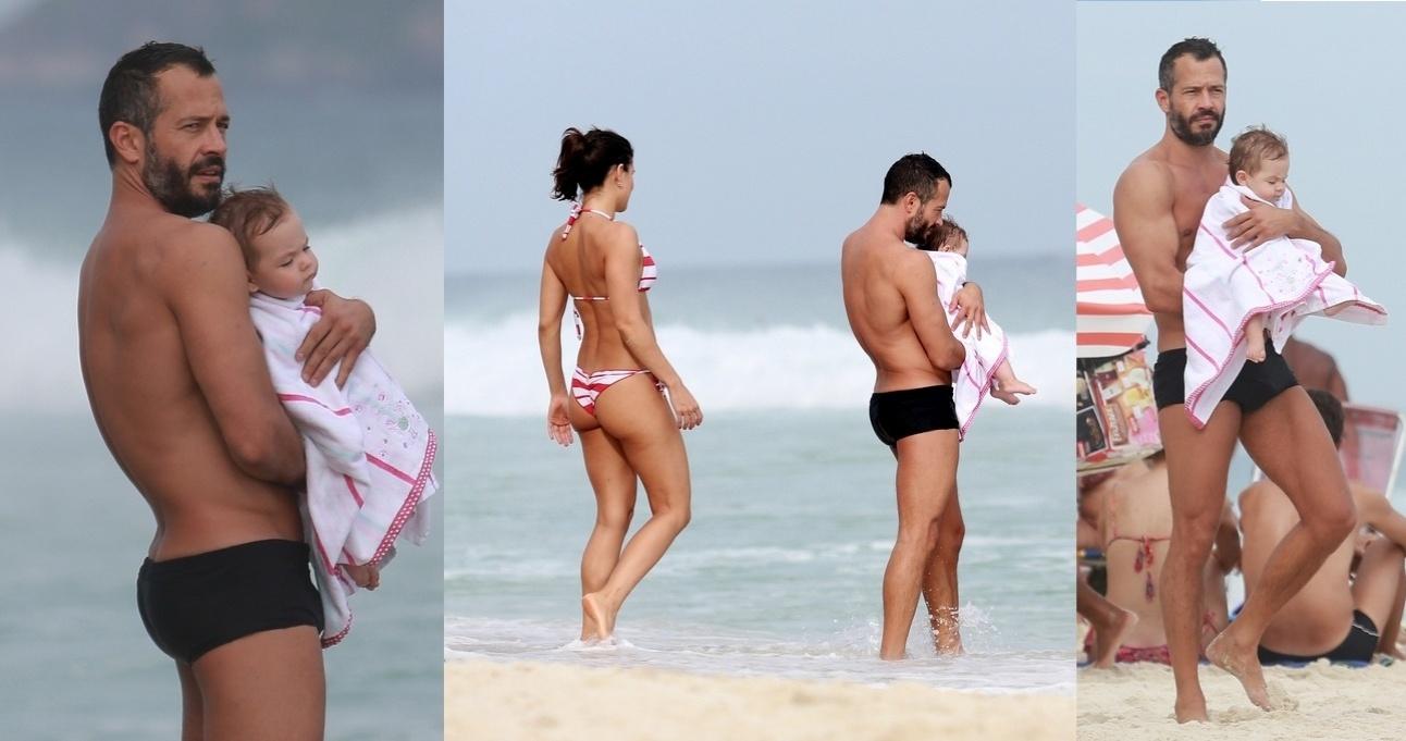 21.abr.2015- Malvino Salvador aproveita feriado na praia da Barra da Tijuca, no Rio, com a mulher Kyra Gracie e a filha Ayra, de sete meses. Durante o passeio, o ator paparicou a caçula, deu mamadeira e a levou para perto do mar