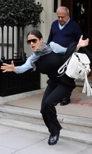 24.abr.2015 - De salto alto, Salma Hayek tropeça e quase cai enquanto desce degraus ao deixar loja de roupas  em Londres, na Inglaterra