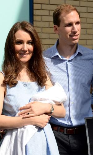 24.abr.2015 - Sósias de William e Kate, Simon Watkinson e Heidi Agan visitam o hospital St Mary, em Londres, na Inglaterra, antes do nascimento do segundo filho do duque e duquesa de Cambridge. Os dois, que seguravam um boneco para representar o irmão do príncipe George, se tornaram uma atração para os fãs que aguardam pela chegada do bebê real