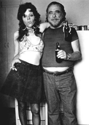 O escritor Charles Bukowski e uma amiga posam para foto, em uma festa em sua casa - Divulgação