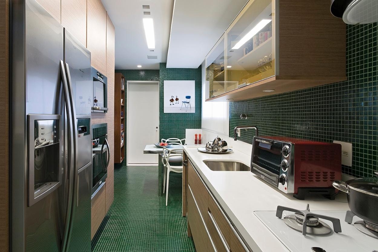 Como uma caixa verde, a cozinha foi revestida inteiramente com pastilhas de vidro da Vidrotil. A marcenaria e os móveis combinam madeira clara e branco, enquanto os eletrodomésticos são majoritariamente em aço. O apê Panamby tem projeto de reforma do arquiteto Diego Revollo