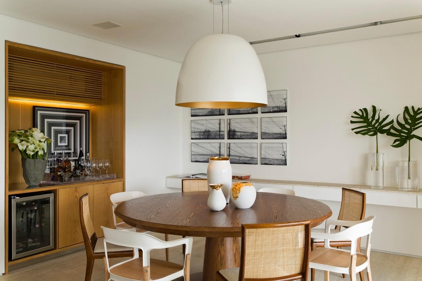O ambiente de jantar é equipado com mesa redonda em carvalho americano, da Vermeil, e cadeiras em dois modelos alternados. A mesma madeira aparece no móvel/ adega (à esq.) que ocupa um nicho na parede. O aparador branco de laca acetinada com tampo de mármore é encimado por uma sequência de fotos em metacrilato, retratando a fiação dos postes da iluminação pública, com autoria de Sachyio Nishimura