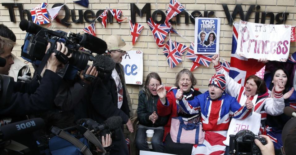 2.mai.2015 - Fãs celebram a chegada da primeira filha de Kate Middleton e Príncipe William em frente ao hospital St. Mary, em Londres