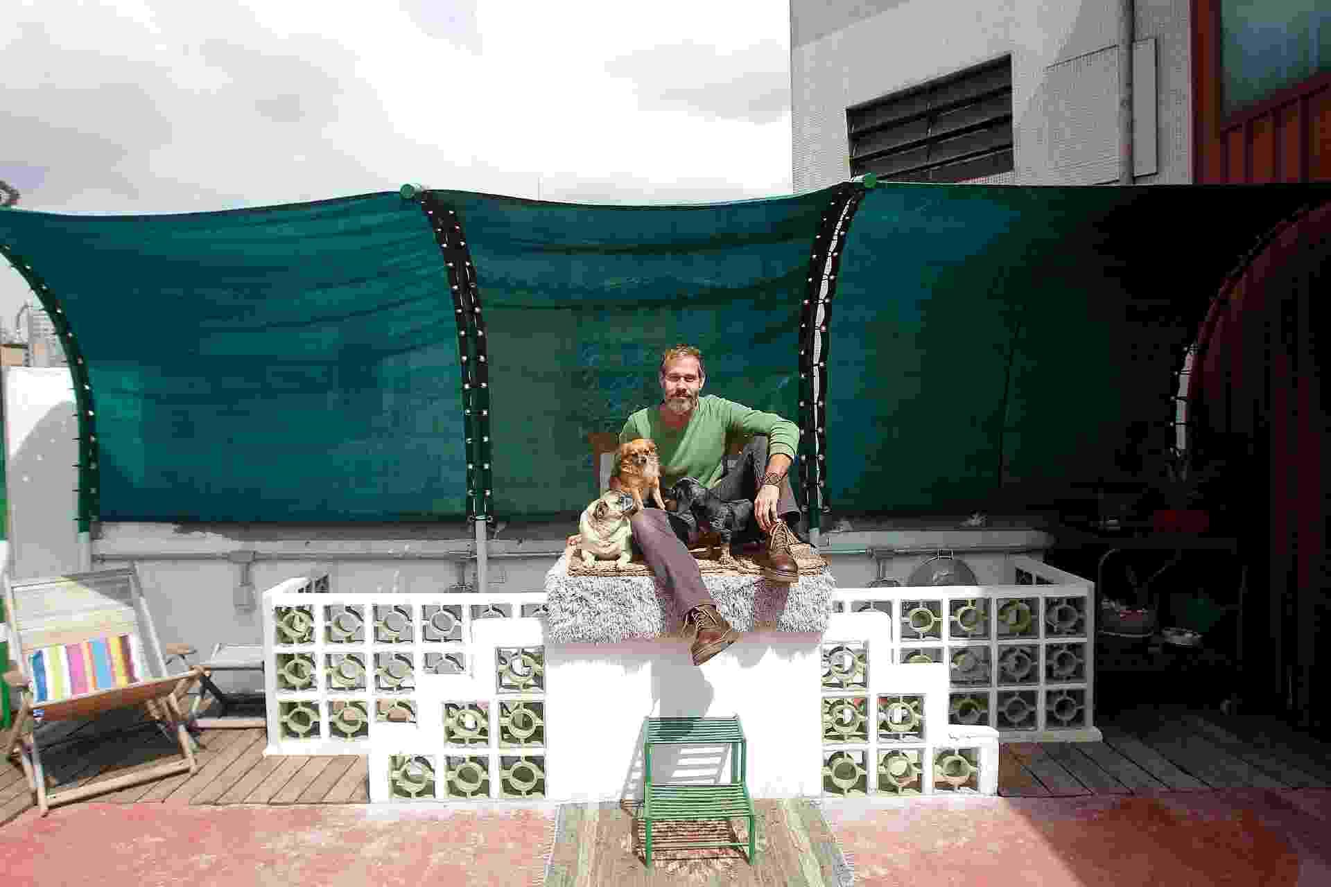 Nico Puig posa junto com seus três cães. O ator se dedica paralelamente ao design e decidiu trabalhar com o reúso e a reciclagem de materiais, decorando - inclusive - seu apê quase exclusivamente com itens achados e comprados a baixíssimo custo - Reinaldo Canato/ UOL