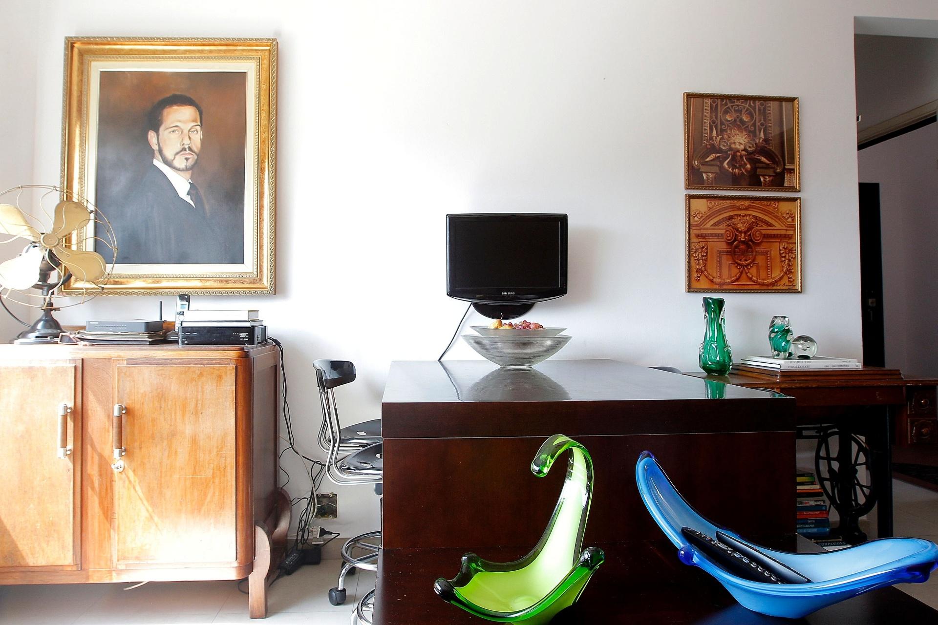 A mesa encostada à parede acomoda quatro convivas em um jantar. À esquerda, um quatro retrata o ator Nico Puig encarnando um de seus personagens. Entre os objetos e móveis antigos, destaque para o ventilador e para a máquina de costura