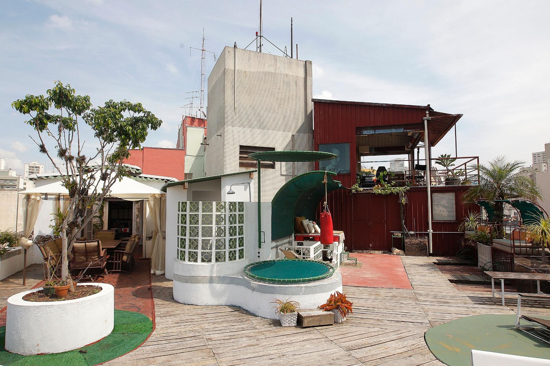 Uma hidromassagem fica coberta com um aro metálico giratório, fechado por tela e serve (também) para armazenar água da chuva, usada na lavagem da área externa e na rega das plantas. O aro superior também é giratório e serve para sombrear o chuveiro, ao lado, protegido pela parede composta por cobogós. O apartamento do ator Nico Puig fica em São Paulo