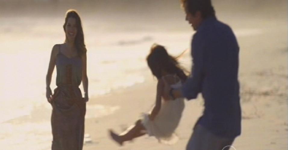 Ao lado de Laura, Caíque brinca com a filha na praia