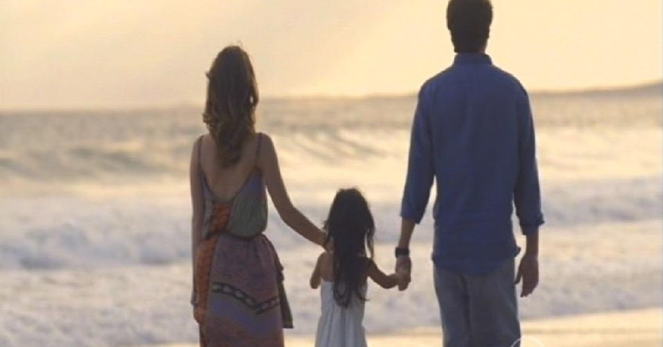 Em cena final, Laura e Caíque caminham com a filha na praia