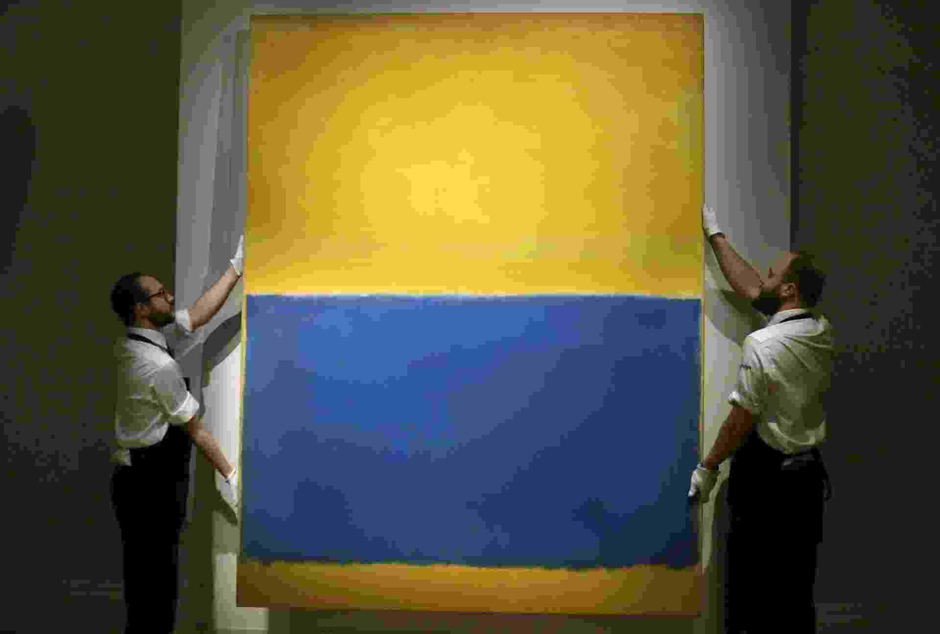 """Funcionários da casa de leilão Sotheby's, em Londres, exibem a pintura """"Sem Nome"""" (Amarelo e Azul), do norte-americano Mark Rothko, no dia 10 de abril. Em leilão realizado na unidade de Nova York da Sotheby's, a obra foi arrematada por US$ 46,5 milhões (quase R$ 140 milhões). Por dez anos, o quadro ficou pendurado na National Gallery de Washington - AP/1998 Kate Rothko Prizel & Christopher Rothko/Artists Rights Society (ARS), New York, Tim Ireland"""