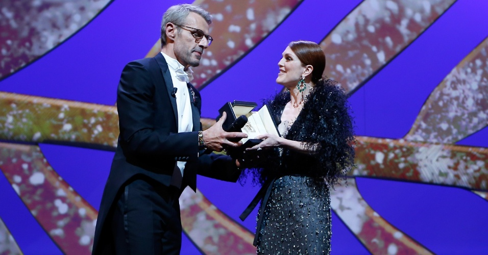 13.mai.2015 - O ator Lambert Wilson, mestre de cerimônia do Festival de Cannes 2015, entrega o prêmio de melhor atriz de 2014 a Julianne Moore, que venceu no ano passado por