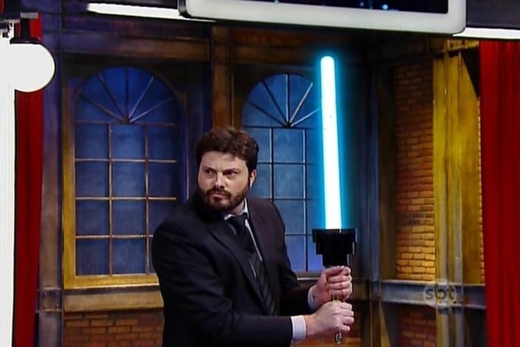 """13.mai.2015 - Marília Gabriela e Danilo Gentili lutam com espadas de Jedi no palco do """"The Noite"""". A arma, que ficou famoso na saga """"Star Wars"""", era um troféu imprensa virado de cabeça para baixo"""