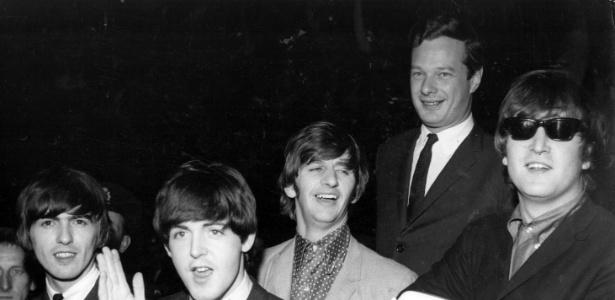 O empresário Brian Epstein posa com os Beatles no aeroporto de Londres em 1964
