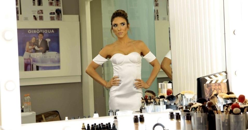 Patrícia Abravanel se observa no espelho após ter maquiagem e penteado finalizados